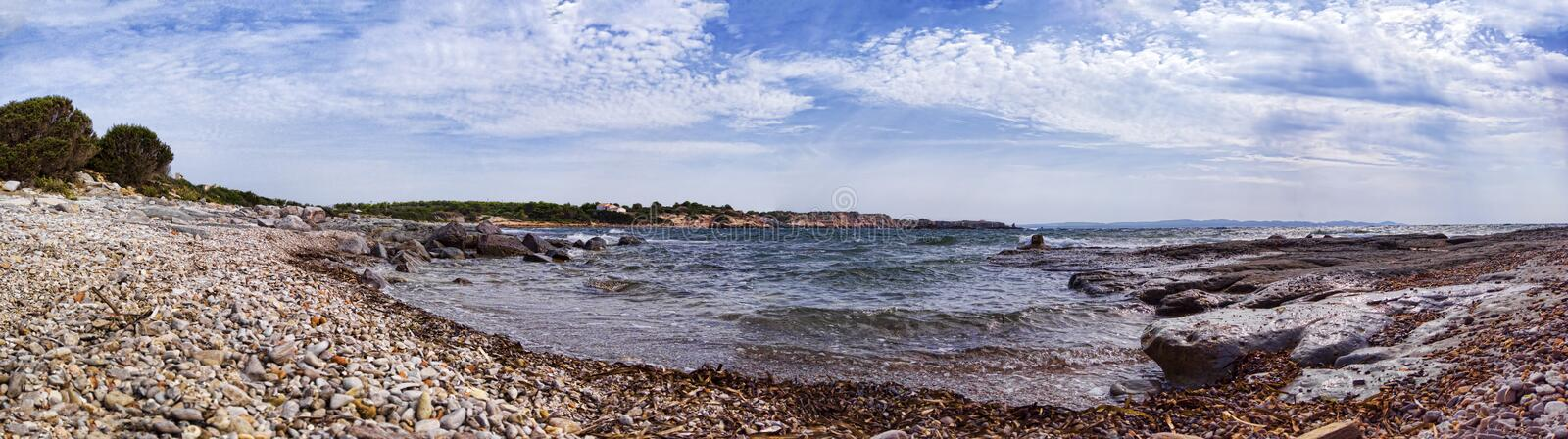 Striking 180 degree panoramic view at wilderness bay in Saint Peter island, rough sea with foam, pebbles beach with rocks smoothed. By the elements in a royalty free stock photo