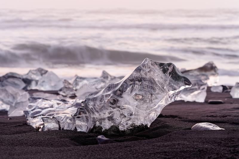 Ice blocks in the evening light. Striking ice formations on a black lava sand beach are highlighted by the evening light with red shades, narrow focus zone royalty free stock photography