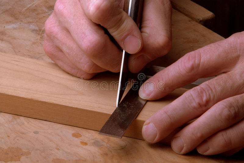 Striking a Line. A woodworker using a marking knife and square to strike a line. Marking for a cut, or for a mortise position. Demonstrating skill and patience royalty free stock photos