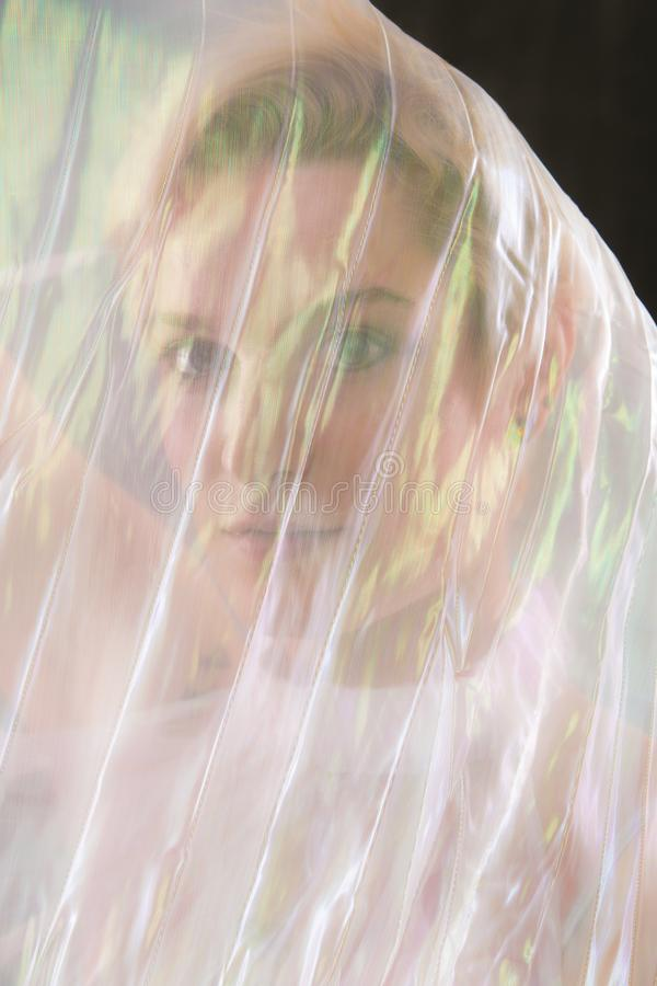 Striking portrait of young woman wrapped in gossamer cape. stock photography