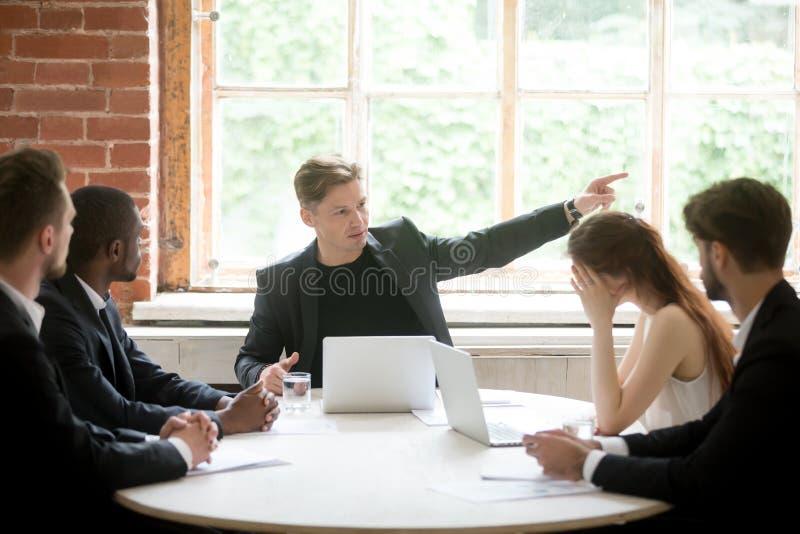 Strikt framstickande som berättar uppriven anställd att lämna rum under förhandsmöte royaltyfri fotografi