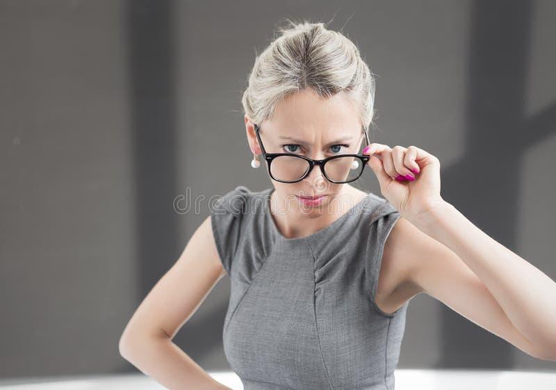 Strikt lärare som ser till och med exponeringsglas med allvarligt uttryck royaltyfri foto