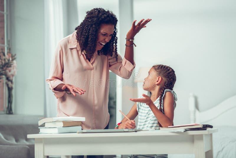 Strikt medio-volwassen Afro-Amerikaans mamma die bij een kleine bruin-haired dochter schreeuwen stock foto
