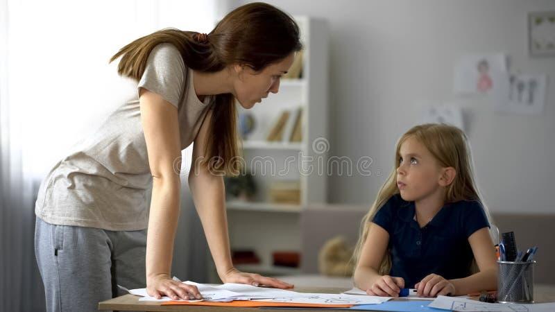 Strikt moder som kritiserar den lilla dottern för teckningar, stressad barndom arkivbild