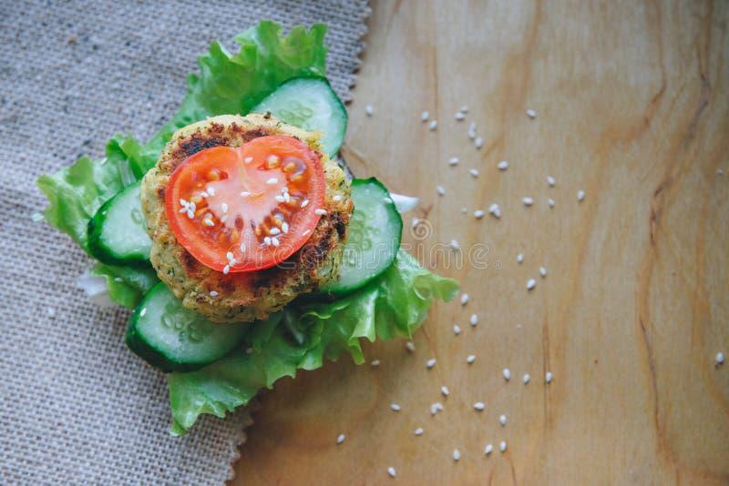 Strikt vegetarian bantar hamburgareaptitretaren med kikärtlinskotletten, gurkan, ny grönsallat och tomaten Stänk med sesam royaltyfria foton