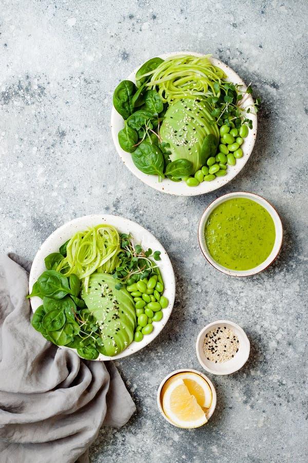 Strikt vegetarian, detoxBuddhabunke med avokadot, spenat, microgräsplaner, edamamebönor, zucchininudlar och grön dressing för ört royaltyfri foto