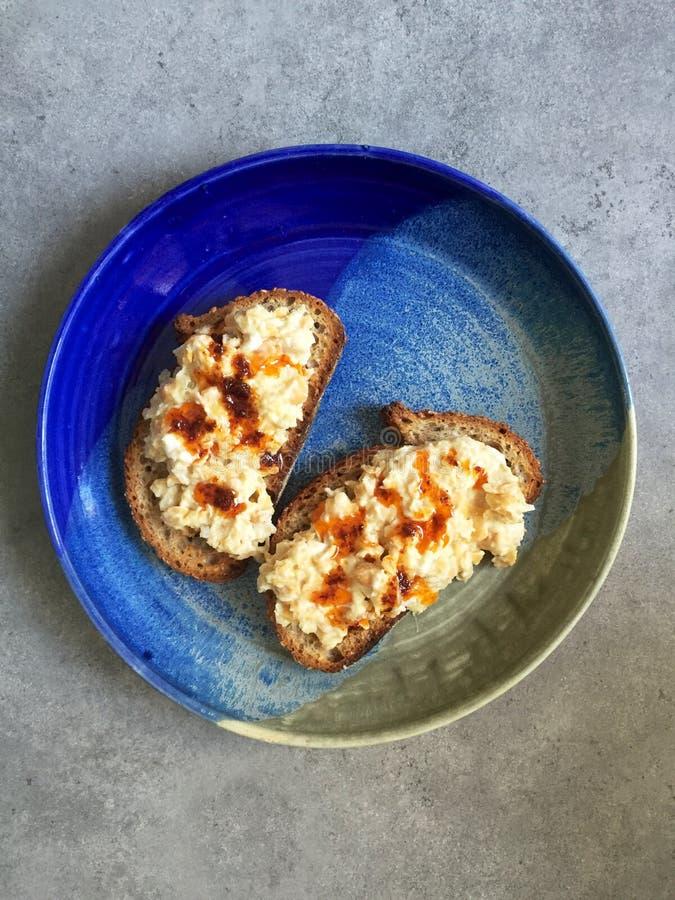 Strikt vegetarian slog kikärtsallad på sourdoughrostat bröd med harissaduggregn arkivfoton