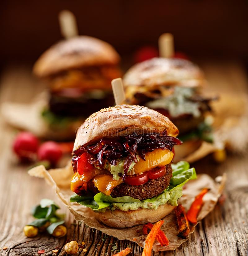 Strikt vegetarianhamburgare, morothamburgare, hemlagad hamburgare med morotkotletten, grillad spansk peppar, körsbärsröda tomater fotografering för bildbyråer