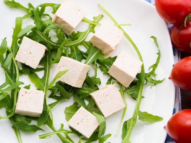 Strikt vegetarianmatbegrepp med tofuen, arugula och tomater arkivbilder