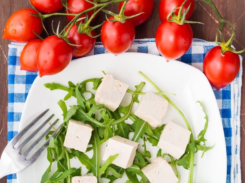 Strikt vegetarianmatbegrepp med tofuen, arugula och tomater royaltyfria bilder