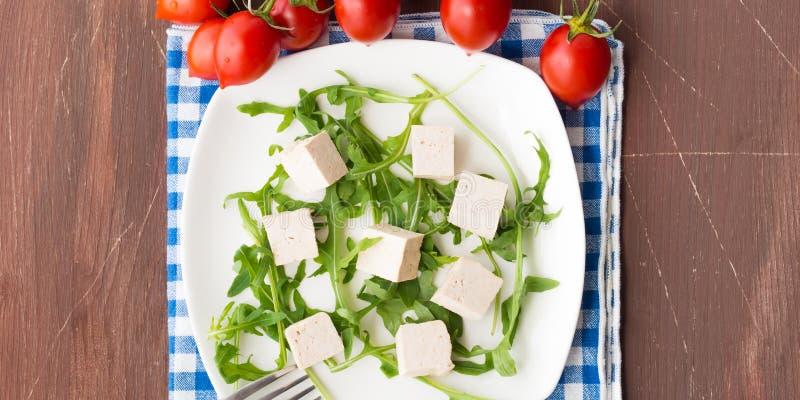 Strikt vegetarianmatbegrepp med tofuen, arugula och tomater royaltyfri bild