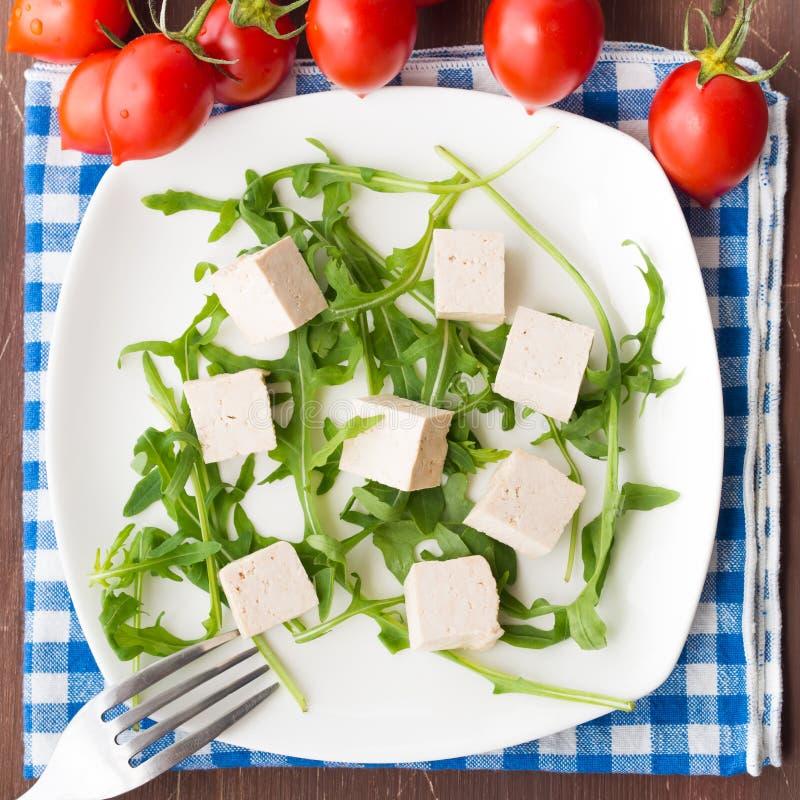 Strikt vegetarianmatbegrepp med tofuen, arugula och tomater royaltyfria foton