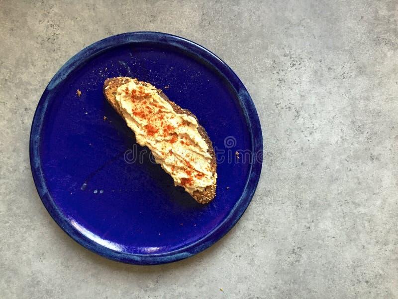 Strikt vegetarianmellanmål: Artisanal helt kornrostat bröd med hummus och paprika arkivfoto