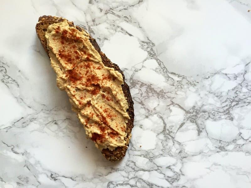 Strikt vegetarianmellanmål: Artisanal helt kornrostat bröd med hummus och paprika royaltyfria foton
