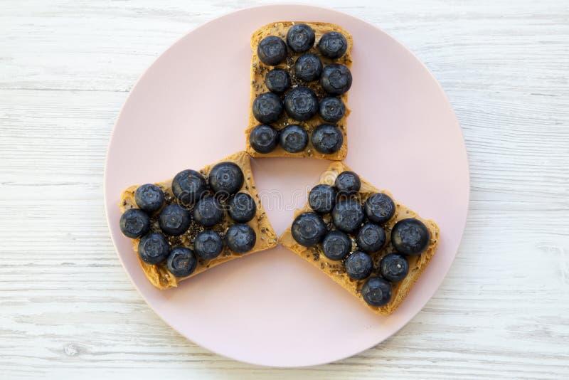 Strikt vegetarianrostade bröd med jordnötsmör, blåbär och chiafrö på en rosa platta över vit träbakgrund, bästa sikt Lekmanna- lä arkivfoton