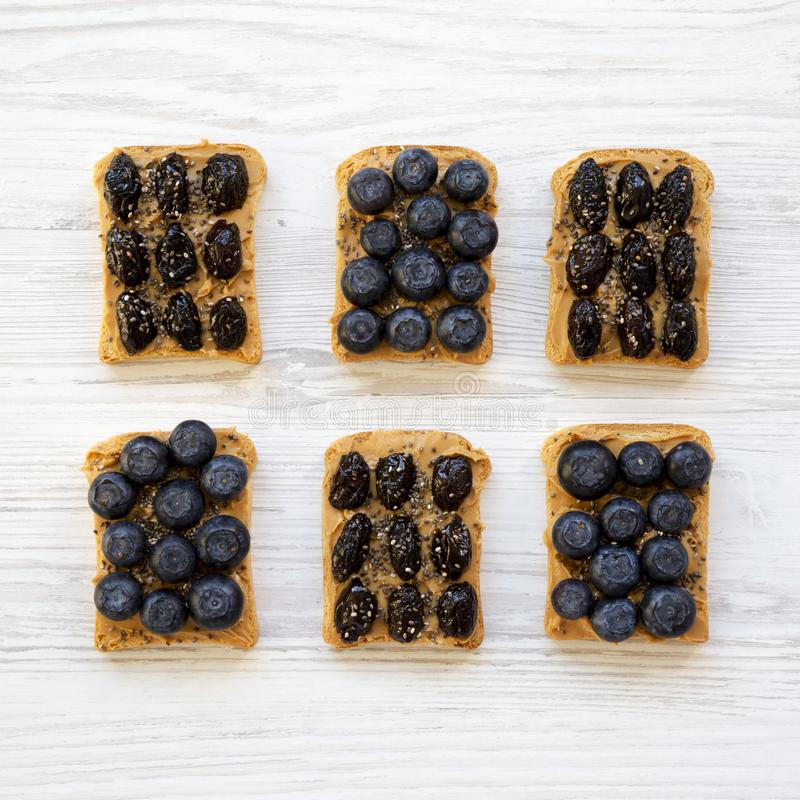 Strikt vegetarianrostade bröd med jordnötsmör, blåbär, oliv och chiafrö på en vit träbakgrund, bästa sikt äta som är sunt plant royaltyfria bilder