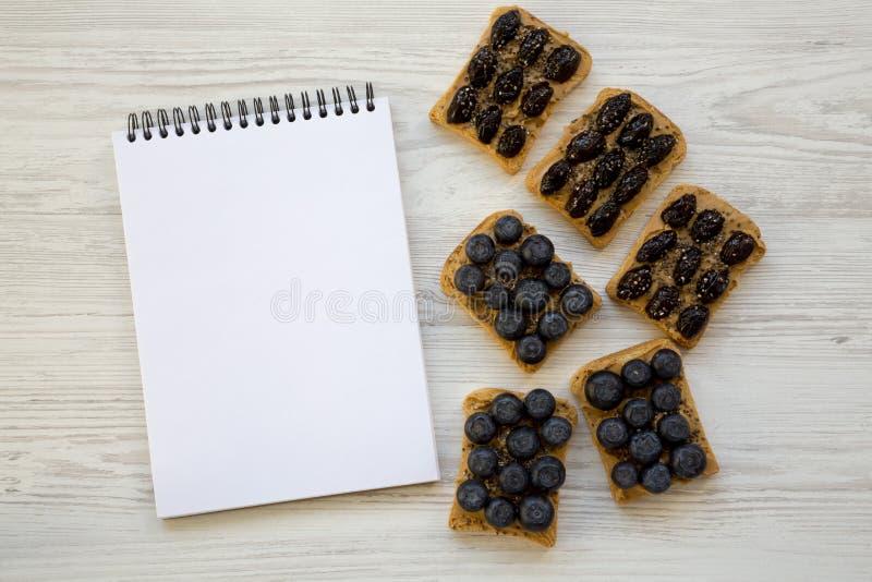 Strikt vegetarianrostade bröd med jordnötsmör, blåbär, oliv och chiafrö på en vit trätabell, över huvudet sikt äta som är sunt pl royaltyfri foto