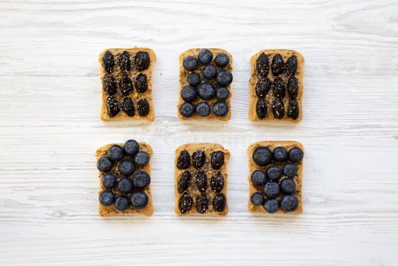 Strikt vegetarianrostade bröd med jordnötsmör, blåbär, oliv och chiafrö på en vit trätabell, bästa sikt äta som är sunt Lekmanna- arkivbild