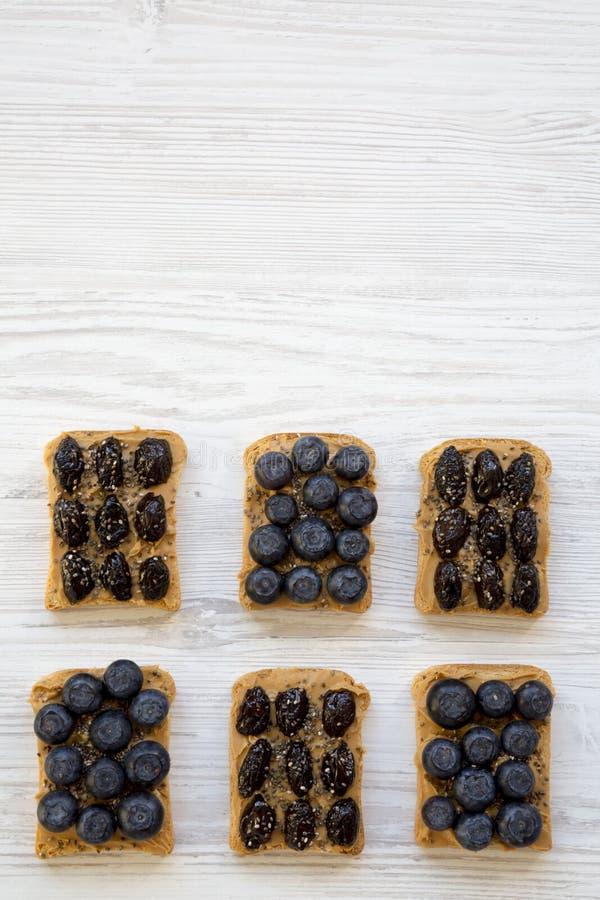 Strikt vegetarianrostade bröd med jordnötsmör, blåbär, oliv och chiafrö på en vit träyttersida, över huvudet sikt äta som är sunt arkivbild