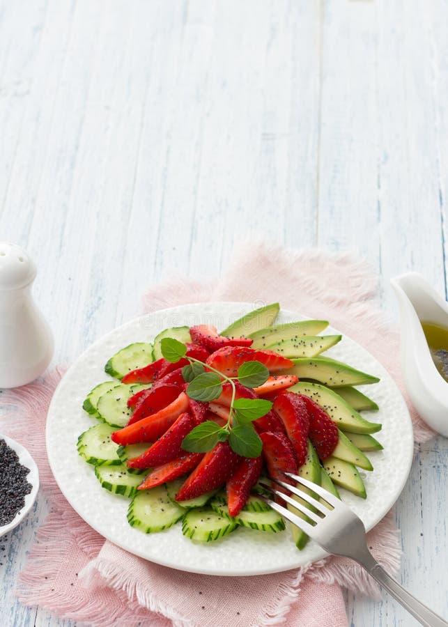 Strikt vegetariansallad från jordgubben, gurkan och avokadot med vallmofrön royaltyfri bild