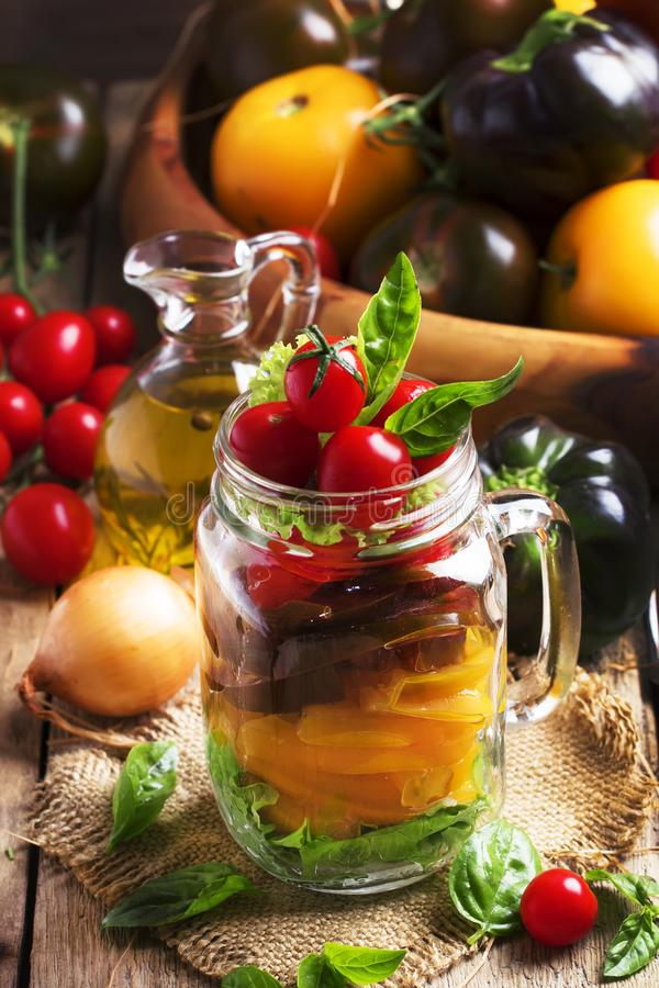Strikt vegetariansalladkrus med gula, svarta och röda körsbärsröda tomater med spanska peppar, lökar, grönsallat, basilika och ol fotografering för bildbyråer