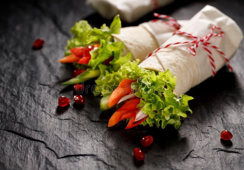 Strikt vegetariantortillan slår in välfyllt med hummus och nya grönsaker arkivfoton