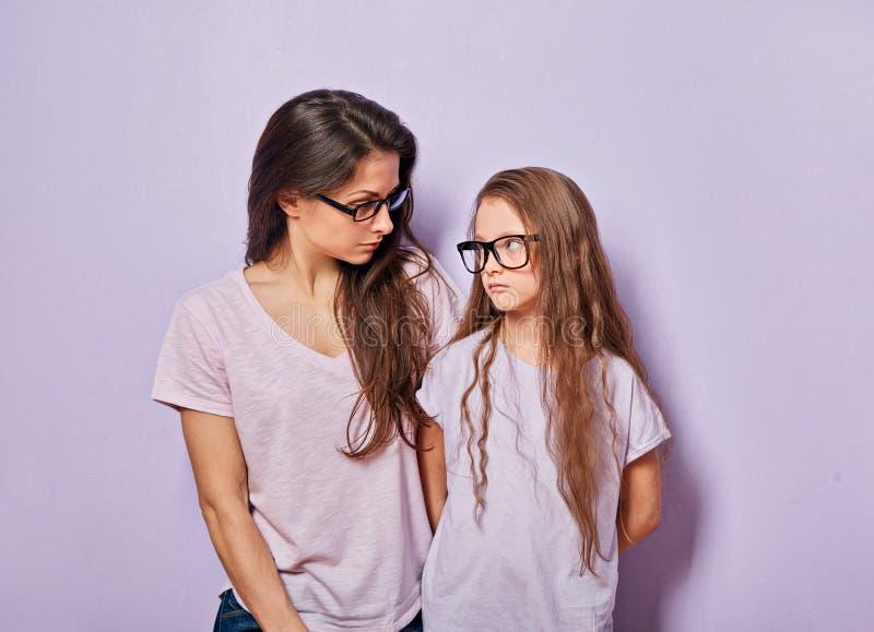 Strikte jonge toevallige moeder die ernstig op haar leuk ongelukkig beledigd jong geitjemeisje op violette muurachtergrond kijken stock foto's