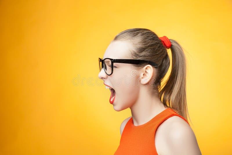 Strikte vrouw die over oranje achtergrond gillen stock afbeelding