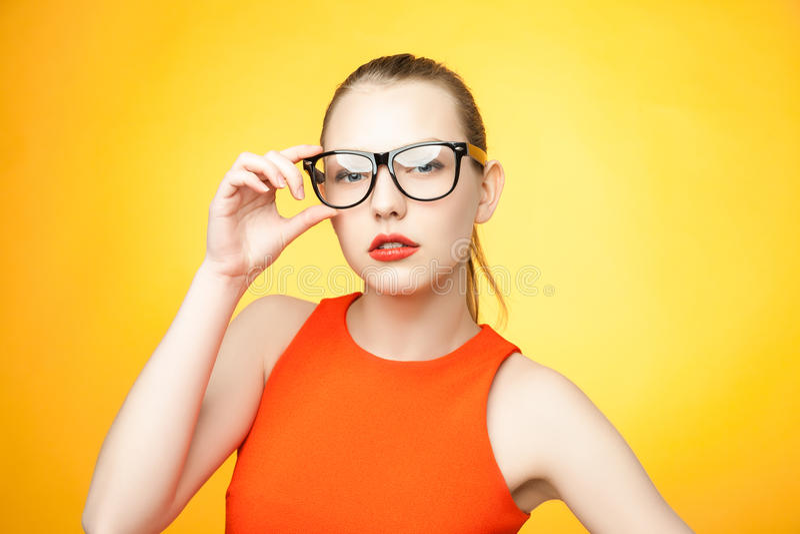 Strikte vrouw in glazen over oranje achtergrond royalty-vrije stock afbeeldingen