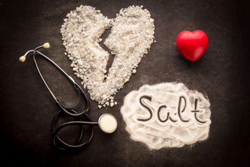 Strilat salt på mörk bakgrund med form för bruten hjärta som göras från salt arkivfoton