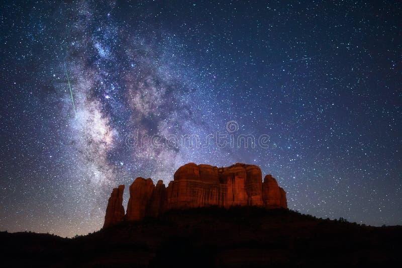 Strimmor för en meteor till och med Vintergatan ovanför domkyrka vaggar i Sedona, Arizona arkivfoto