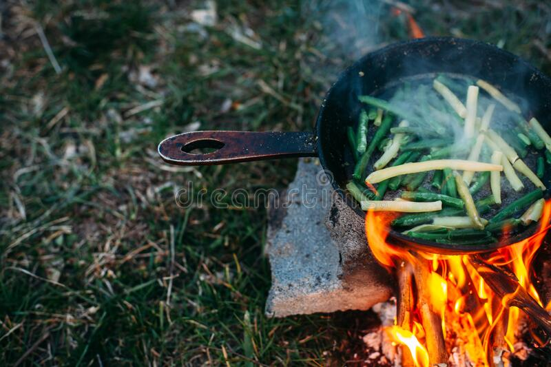 String beans in a pan. Cooking vegetables on an open fire. Food on a camping trip.  stock photography