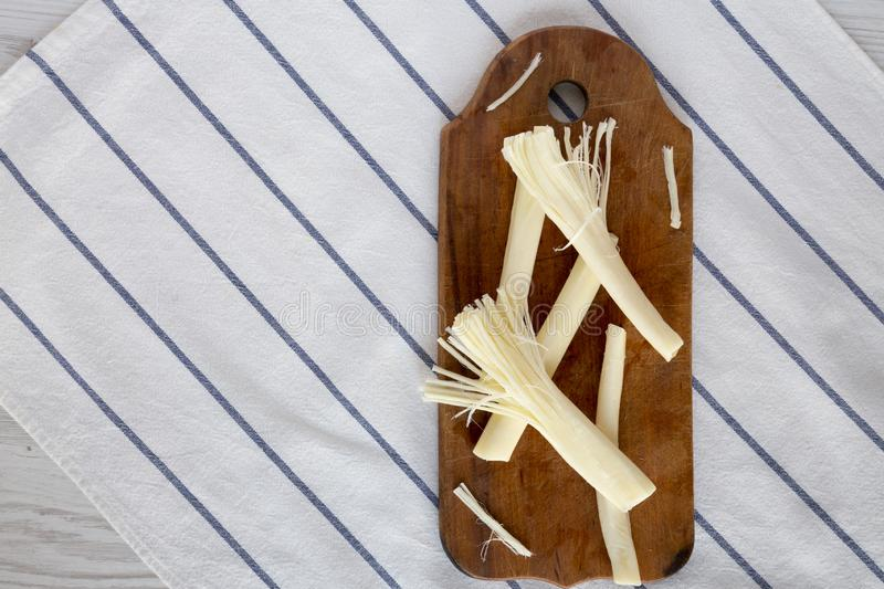 String cheese on rustic wooden board, top view. Healthy snack. Flat lay, overhead, from above stock photo