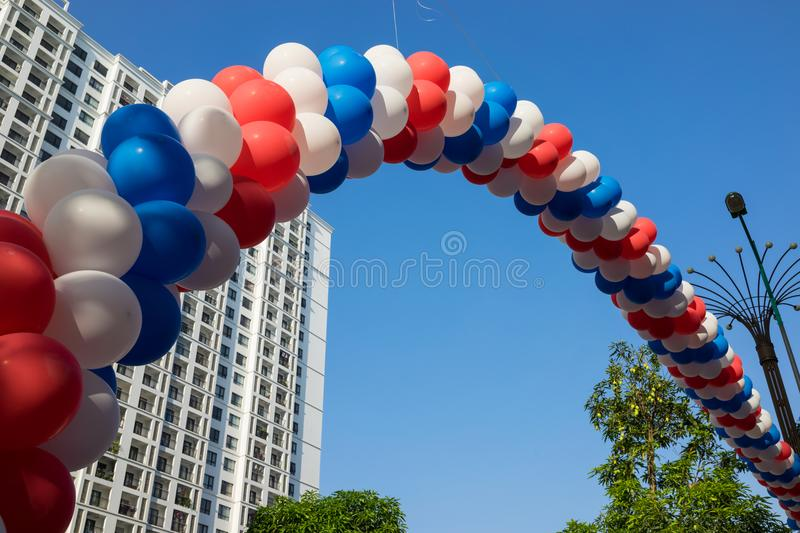 String of colorful balloons against apartment buildings and blue sky on background. Concept of outdoor celebration activities or e. Vent of apartment residents stock photos