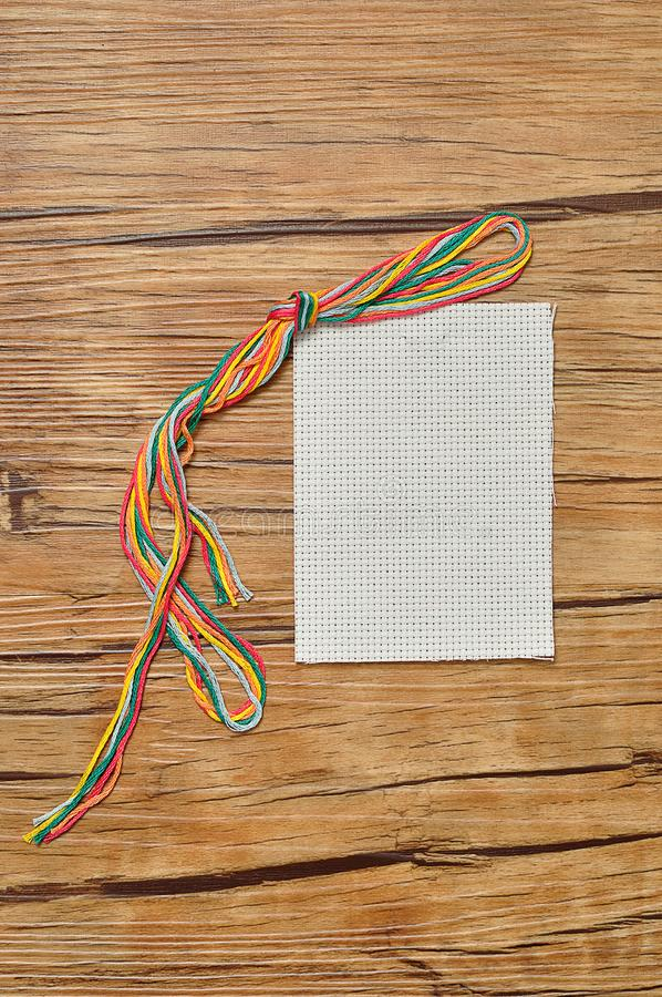 String of colorful embroidery thread displayed with a piece of embroidery fabric royalty free stock image