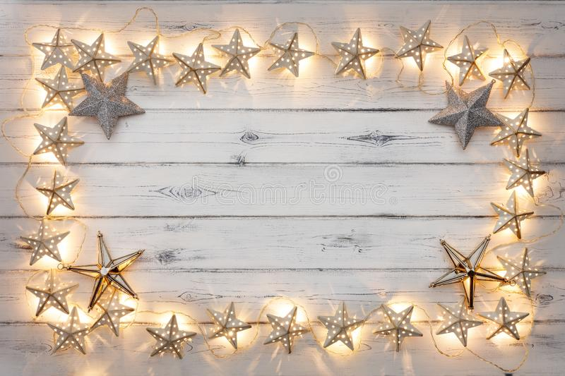 A border of golden star christmas lights, and star baubles, on a stock image