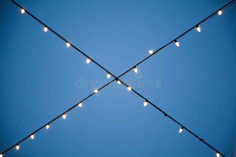 A string of hanging white lights crossing royalty free stock photography