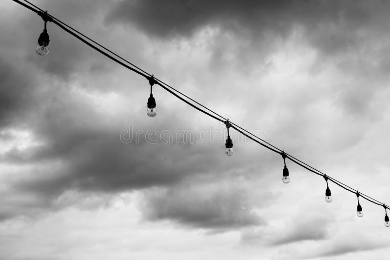 A string of lights in black and white. A picture of a string of lights with clear lights bulbs against the sky in black and white royalty free stock photos