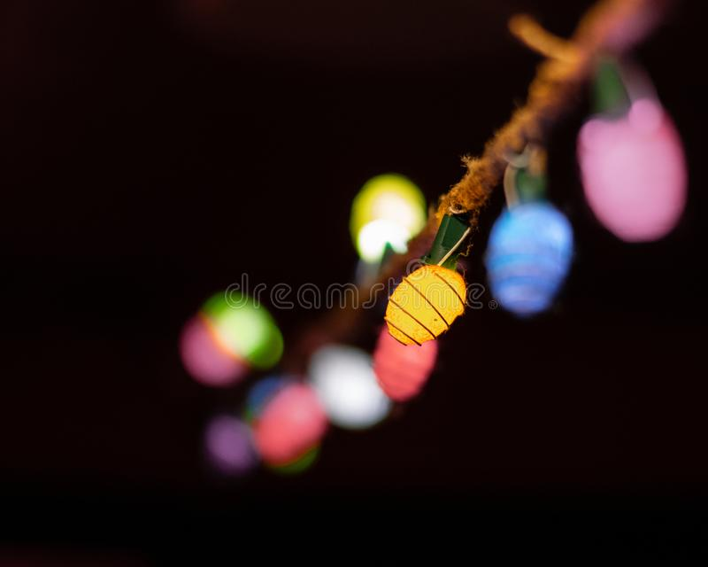 String Lights on Rope. Colored string lights hanging on rope with black background royalty free stock images