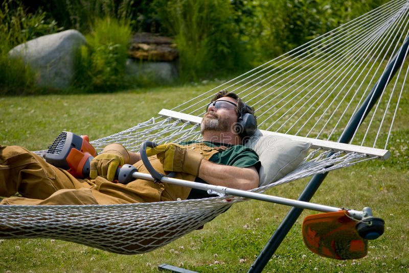 String Trimmer - 3. Man sleeping after a hard days work using the weed trimmer royalty free stock image