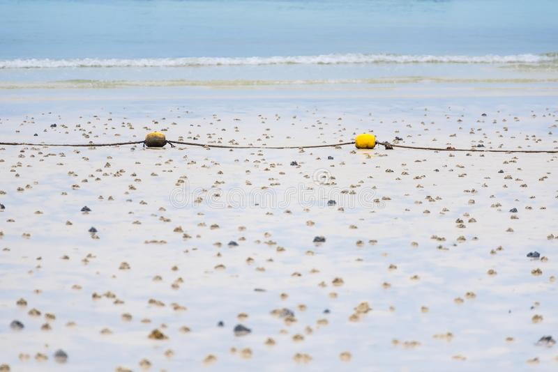 A string of yellow buoys on the beach for safety zoning in the sea.Thailand. Background, blue, boat, boundary, coast, color, day, equipment, fishing, float stock photography