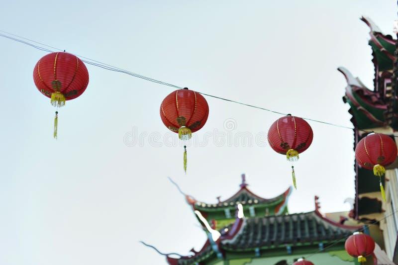 Stringed pappers- lyktor hänger mot de skyStringed pappers- lyktorna hänger från orientalisk utformad byggnad royaltyfria foton