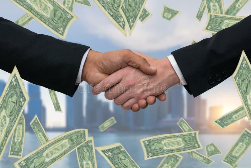 Stringere le mani per un affare di affari con i soldi dei dollari e l'orizzonte delle costruzioni della città nel fondo immagini stock