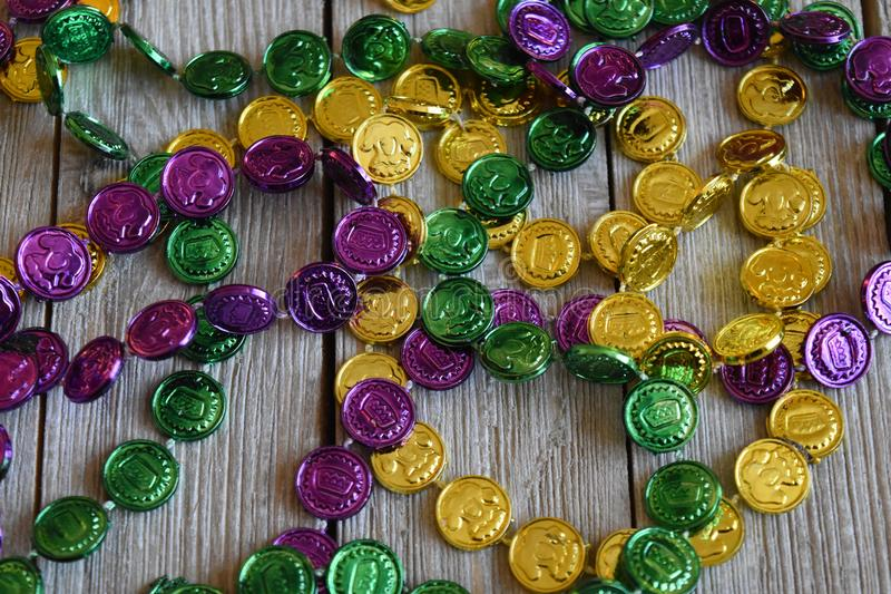 Mardi Gras beads on a wood background stock images