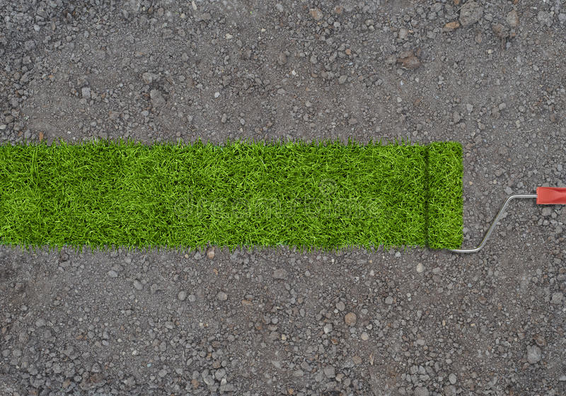 Strip of green grass made by roller for painting on a ground with small stones. royalty free stock photos
