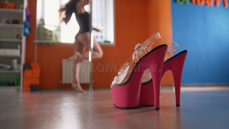 Strip-shoes in front of dancing woman in a fitness class - pink shoes royalty free stock photos