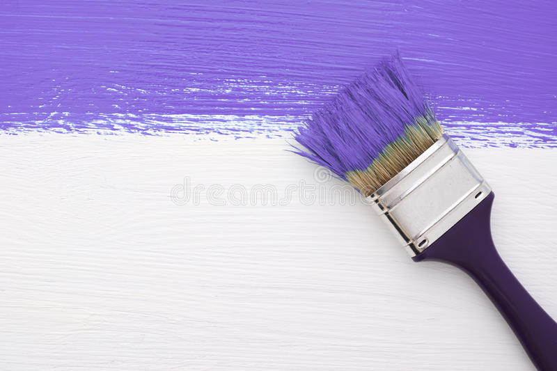 Stripe of purple paint with a paintbrush on white. Horizontal stripe of purple paint with a dirty paintbrush on a white wooden board royalty free stock images