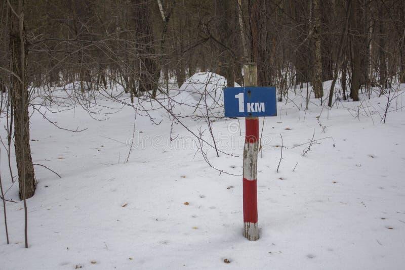 Striped красный штендер знак который говорит ручки 1 километра из снега пр стоковое изображение