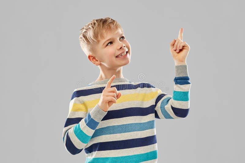 Мальчик в striped пуловере указывая палец вверх стоковое изображение