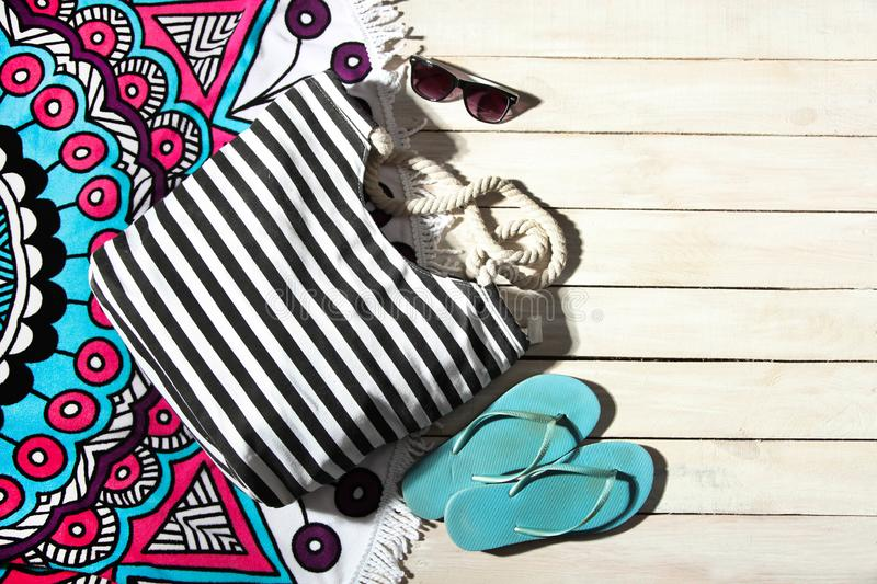 Striped bag, rubber flip flops and bright beach towel stock image